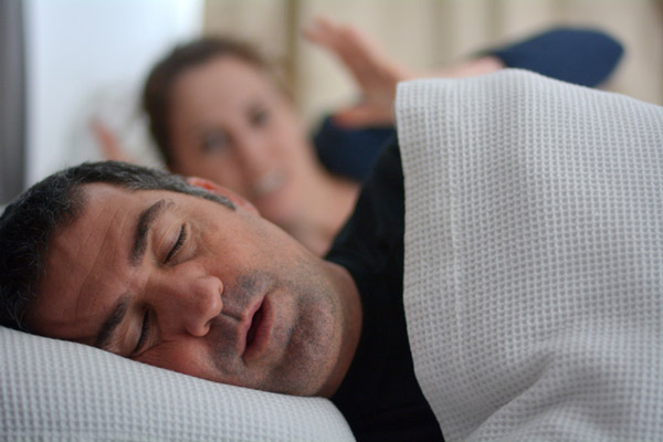 Man snoring in bed while woman covering her ears