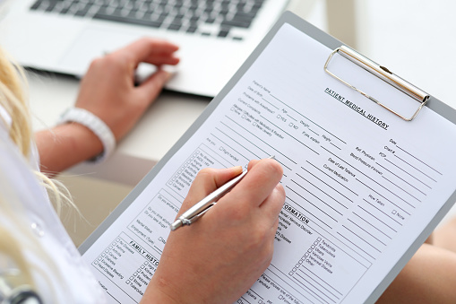 Woman filling out patient form for Downey Oral and Maxillofacial Surgery in Downey, CA